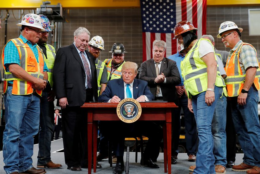 President Donald Trump signs an executive order on energy and infrastructure during a campaign event at the International Union of Operating Engineers International Training and Education Center in Crosby on Wednesday.