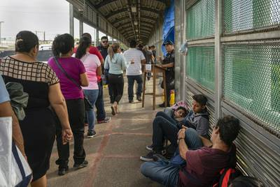 Asylum seekers from Central and South America wait on the Mexican side of the Brownsville's Gateway International Bridge.