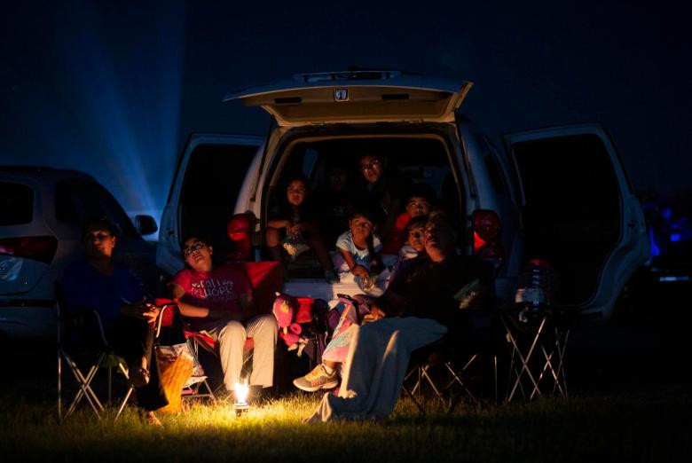At left, Marta Linares and her family watch a movie at the WesMer Drive-In Theatre in Mercedes. They have been coming to the theatre once a month for the past 15 years.