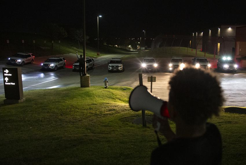 Renee White, left, holds up a fist in front of the barricade of eight police cars as Elijah Lyons, Marvin Scott III's 9-year…