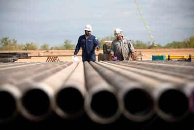 Rig workers inspect casings that will be loaded into the well in preparation for the hydraulic fracturing process at a Chesapeake Energy drill site in Dimmit.