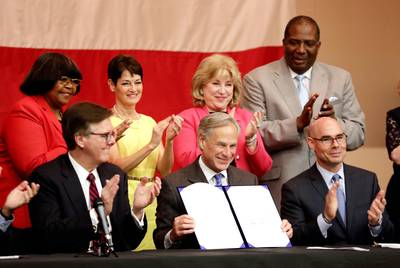 Gov. Greg Abbott, center, holds up House Bill 3, the school finance bill, after signing it into law at an Austin elementary school on June 11, 2019.