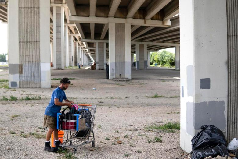 """Anthony Graham, 55, who is known as """"Tigger"""" and has been unhoused for twelve years, packs up belongings from his cart at an encampment underneath Ben White Blvd. on July 27, 2021.  Source diversity info: White Male"""