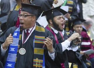Graduates react after hearing billionaire technology investor and philanthropist Robert F. Smith say he will provide grants to wipe out the student debt of the entire 2019 graduating class at Morehouse College in Atlanta, Sunday, May 19, 2019.