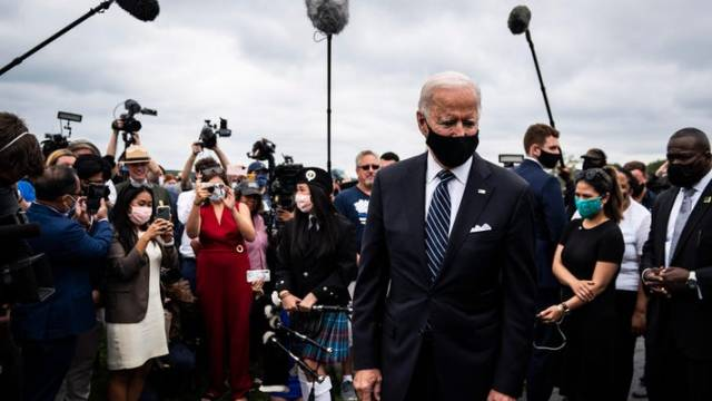 President Joe Biden looks at something off camera as the media gathers behind him