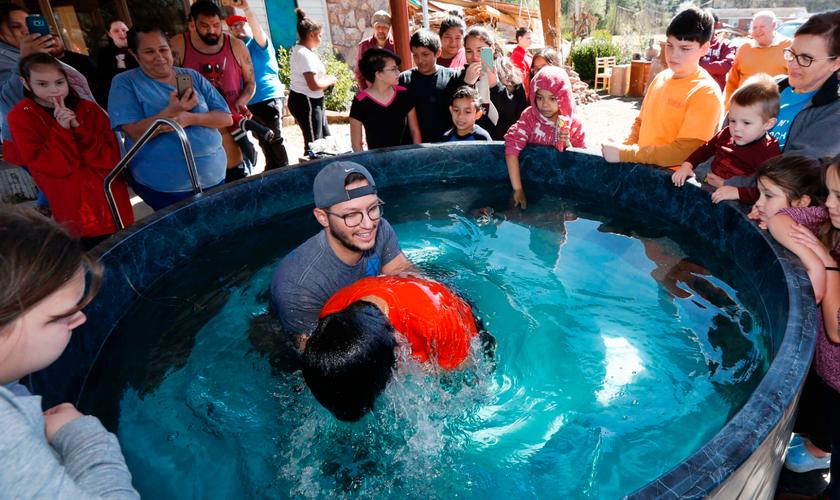 O pastor de jovens, Craig Blaylock, batiza membro da igreja que foi atingida por um tornado. (Foto: AP/Rogelio V. Solis)