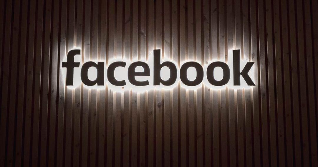 Le logo Facebook illuminé sur un mur.