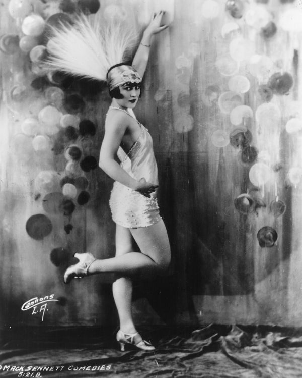 flapper with feathered headress and short dress