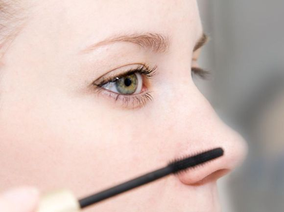 A woman applying mascara to her eyes