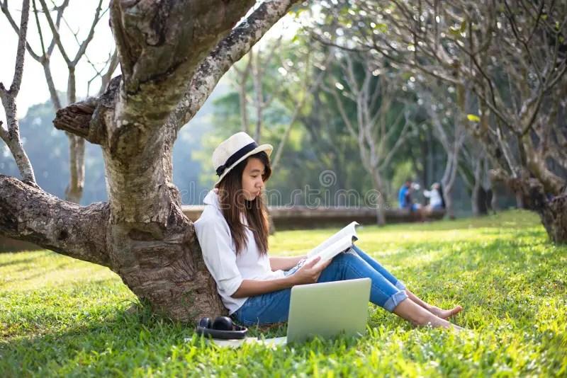 La Muchacha Goza El Leer De Un Libro Debajo Del árbol