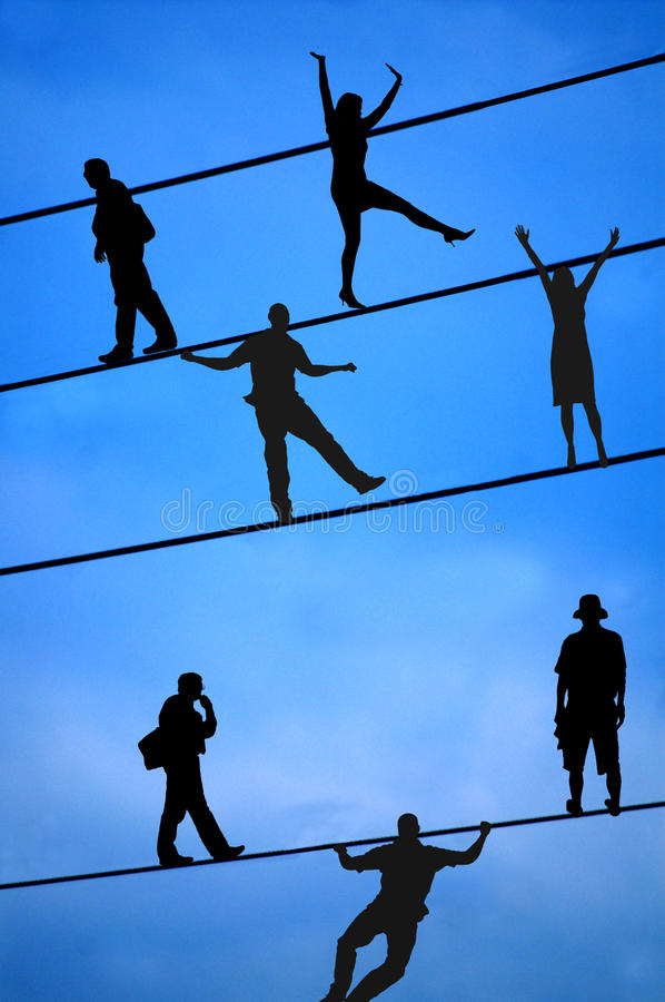 People Balancing On Tight Wire Stock Photo