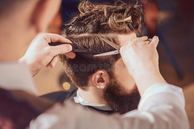 Professional Barber Styling Hair Of His Client Stock Photo