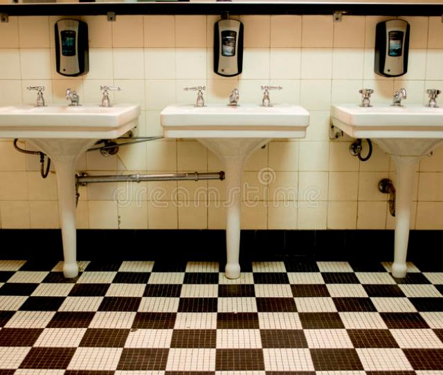 Three White Porcelain Sinks In An Old Art Deco Public Bathroom With A Black And White Checkered Tile Floor