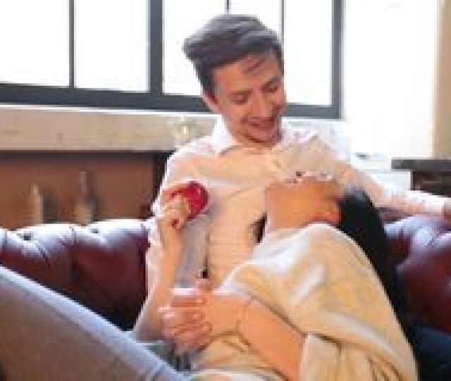 A Happy Couple Jokes Before Having Sex On The Couch In The Living Room At Home