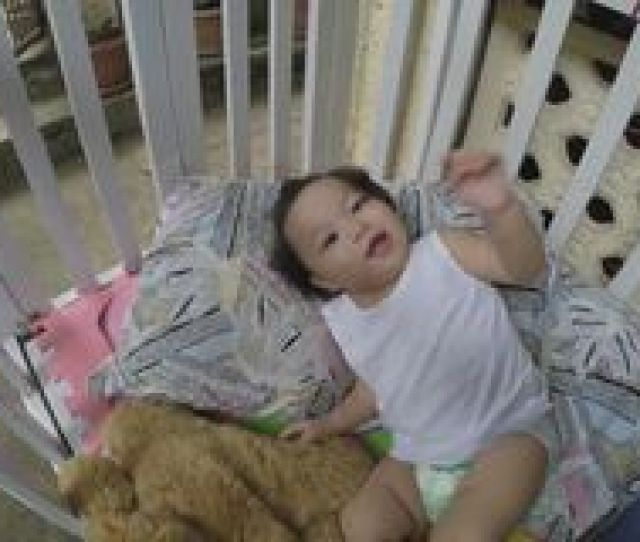 Baby Girl Playing By Herself In Crib Stock Video Footage