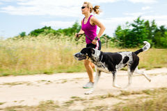 Woman runner running, walking dog in summer nature Stock Photography
