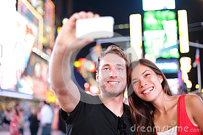 Dating young couple happy in love taking selfie photo on Times Square, New York City at night. Beautiful young multiracial tourist