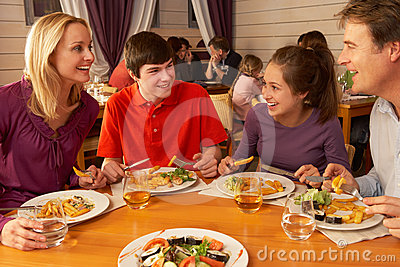 Family Eating Lunch Together In Restaurant Stock Images