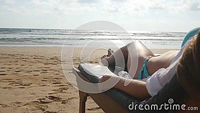 jeune femme se trouvant sur le lit pliant par la mer et le bronzage corps feminin sur la chaise longue detendant et appreciant pe banque de videos video