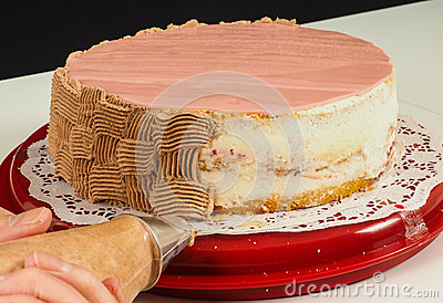 Professional cake baker piping chocolate cream onto cake