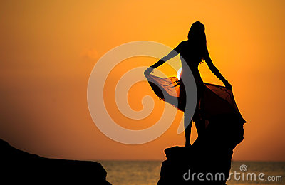 A silhouette of a young girl on rock at sunset 1