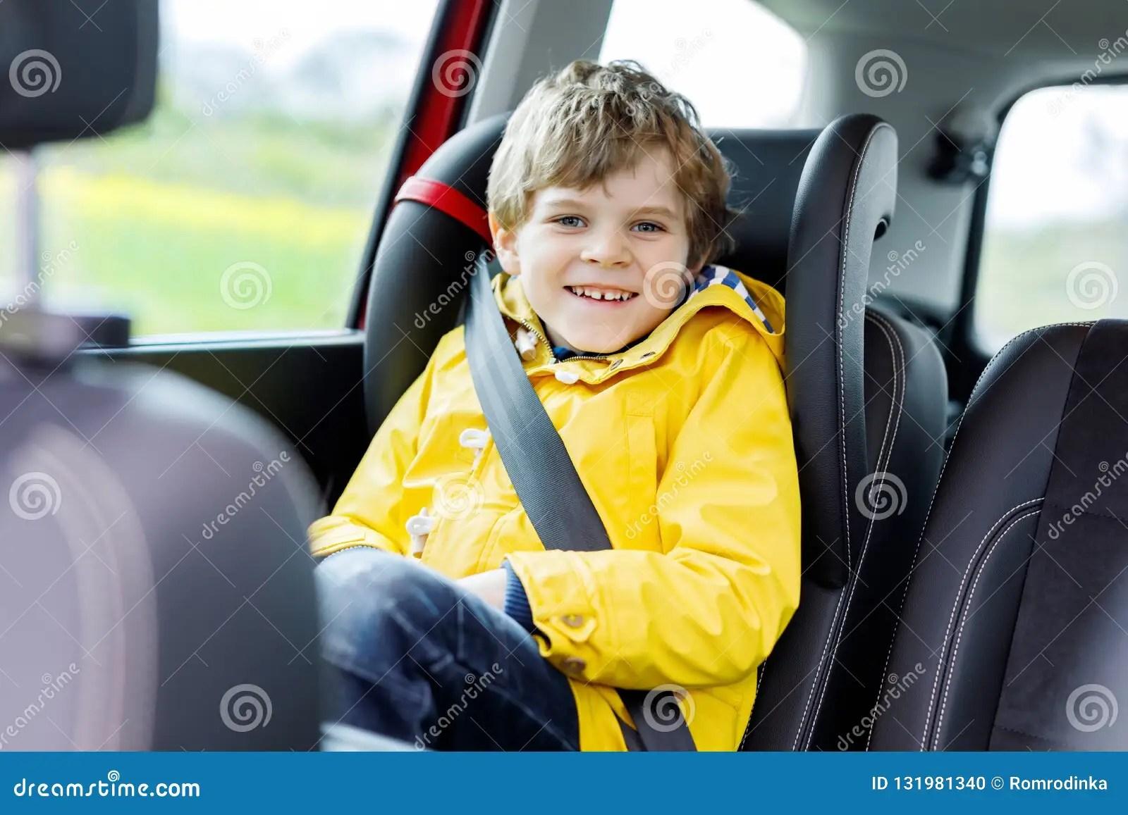 Adorable Cute Preschool Kid Boy Sitting In Car In Yellow