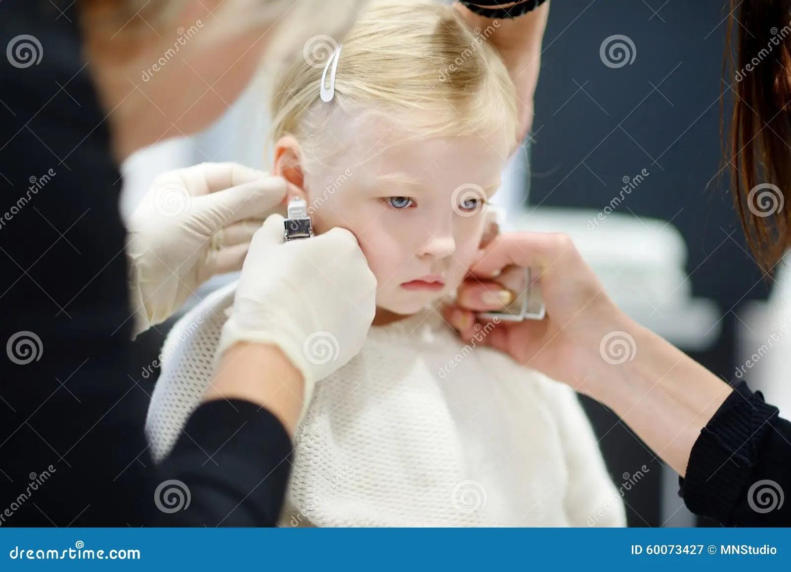 Adorable Little Girl Having Her Ears Pierced Stock Photo