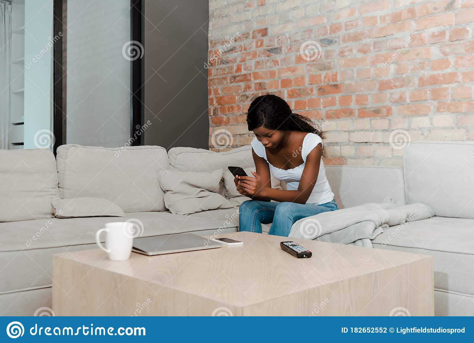 african american woman with digital tablet on sofa near coffee table with laptop smartphone remote controller and cup stock photo image of leisure communication 182652552