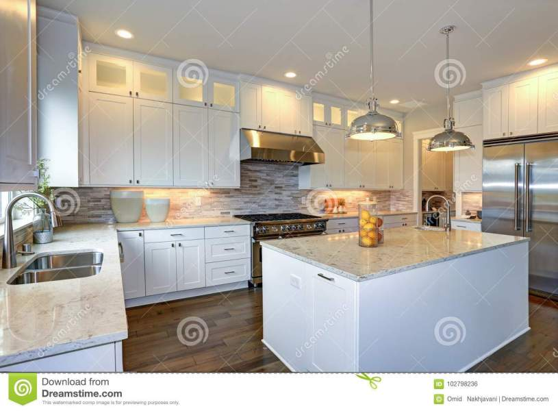 Luxury White Kitchen With Large Kitchen Island  Stock Photo   Image     Amazing white kitchen design with white shaker cabinets paired with white  and gray marble counters  large White kitchen peninsula with a sink and  hardwood