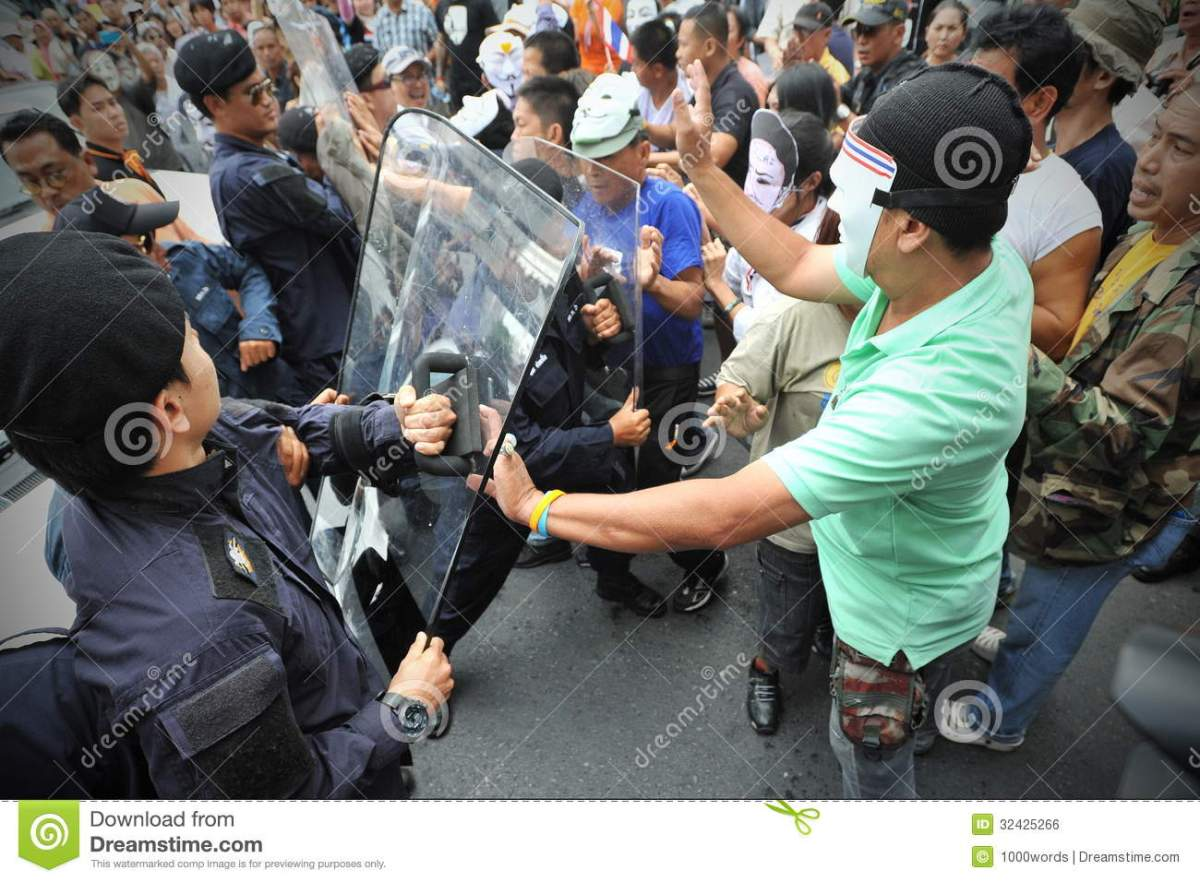 Masked protesters scuffle with riot police during an anti-governmtne rally in Bangkok.
