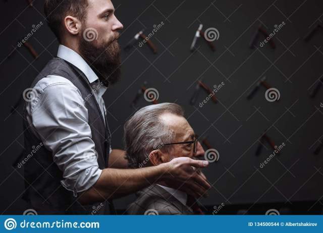 bearded old businessman sitting at barber shop in chair