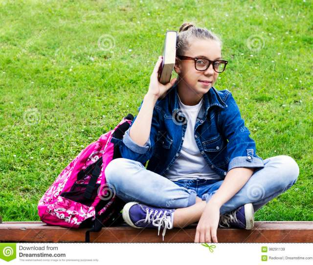 Beautiful Blonde Schoolgirl Girl In Jeans Shirt Reading A Book On Grass With A Backpack In