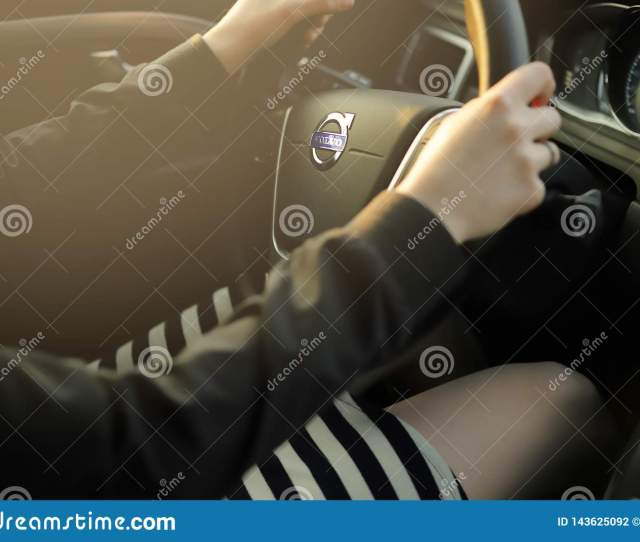 A Beautiful Woman In Short Striped Skirt Is Driving A Volvo Car In Bright Sunlight