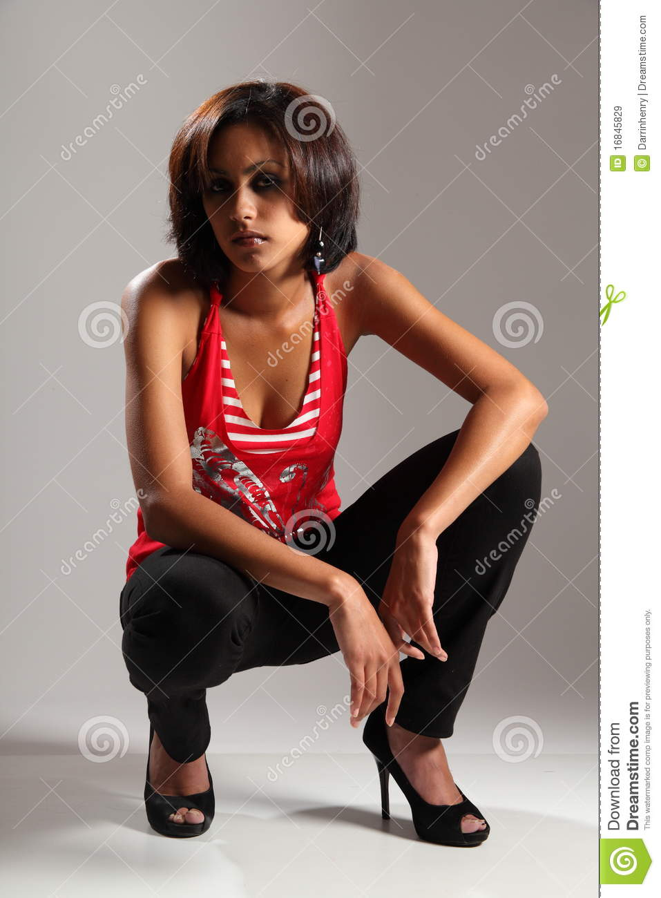 Beautiful Young Slim Girl Crouching In Studio Stock Image