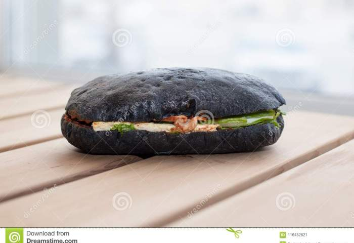 Black Bread Sandwich With A Fish Isolated On On Wooden Surface Stock