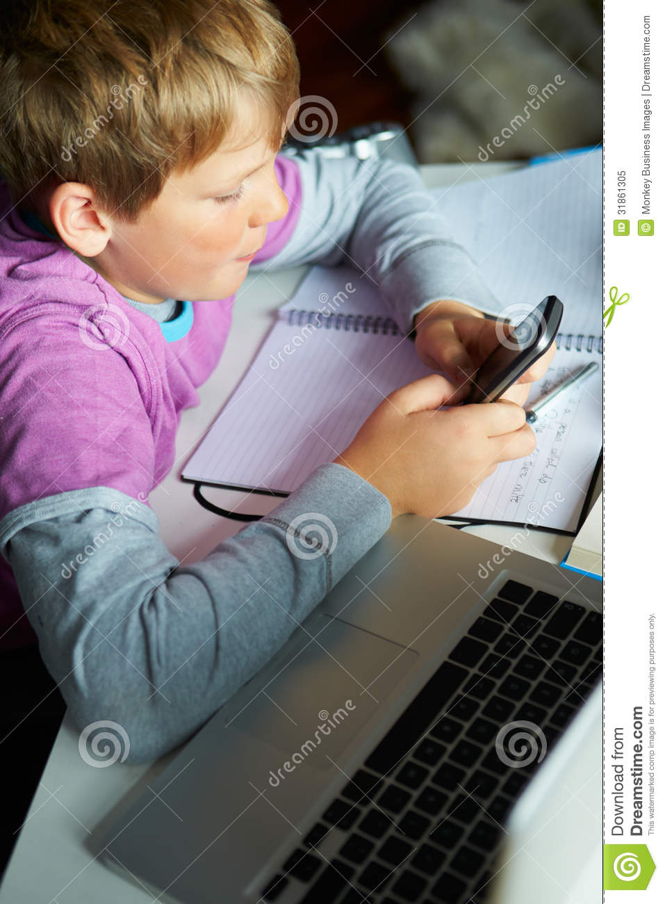 Boy Using Mobile Phone Instead Of Studying In Bedroom