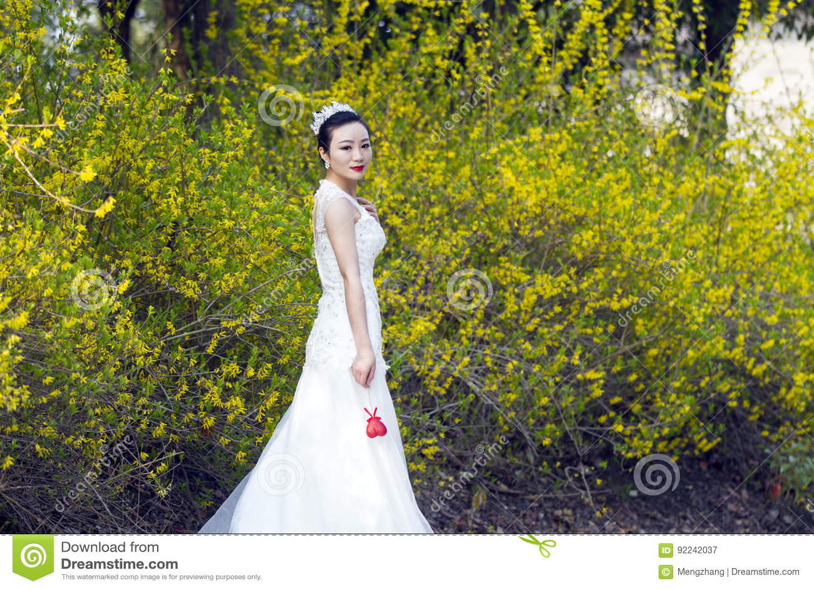 A Bride With White Wedding Dress Stand By Golden Jasmine