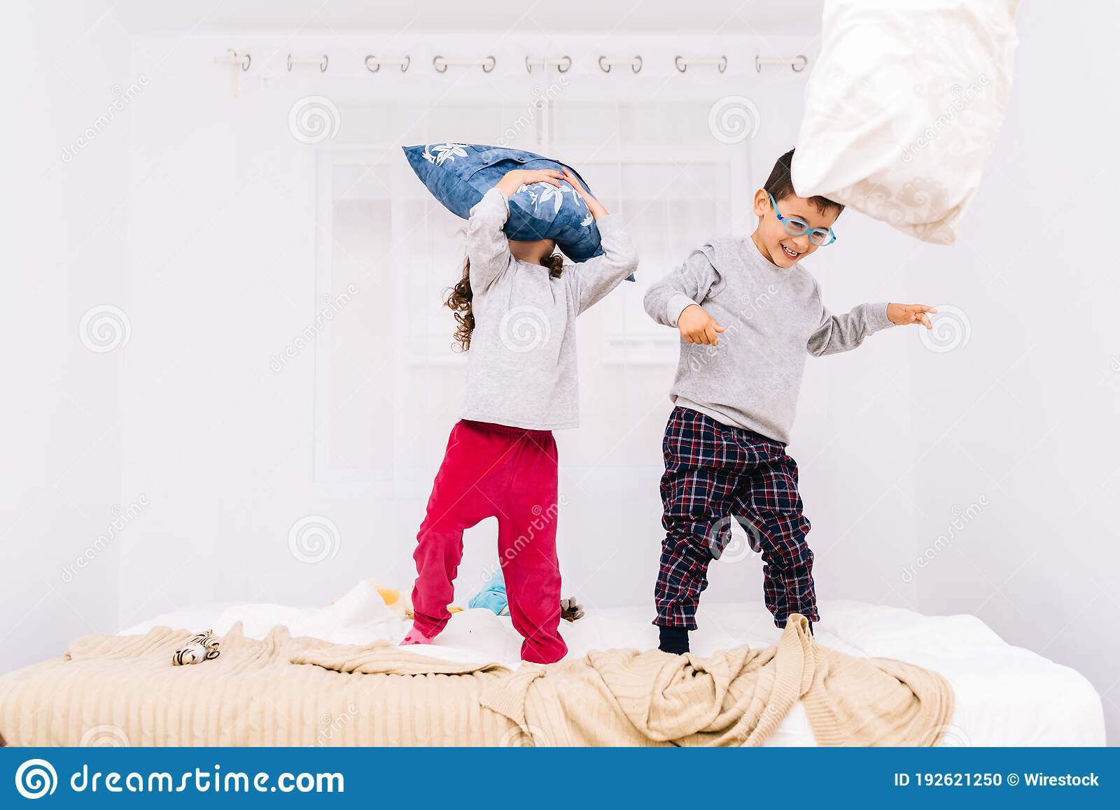 cheerful children with glasses jumping and playing with pillows on the bed stock photo image of pillow playing 192621250