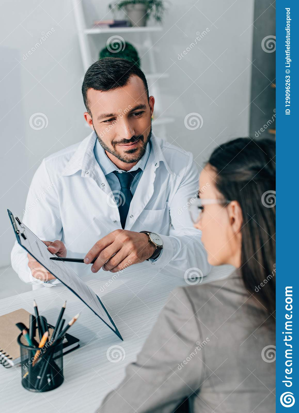 Cheerful Doctor Pointing On Insurance Claim Form To