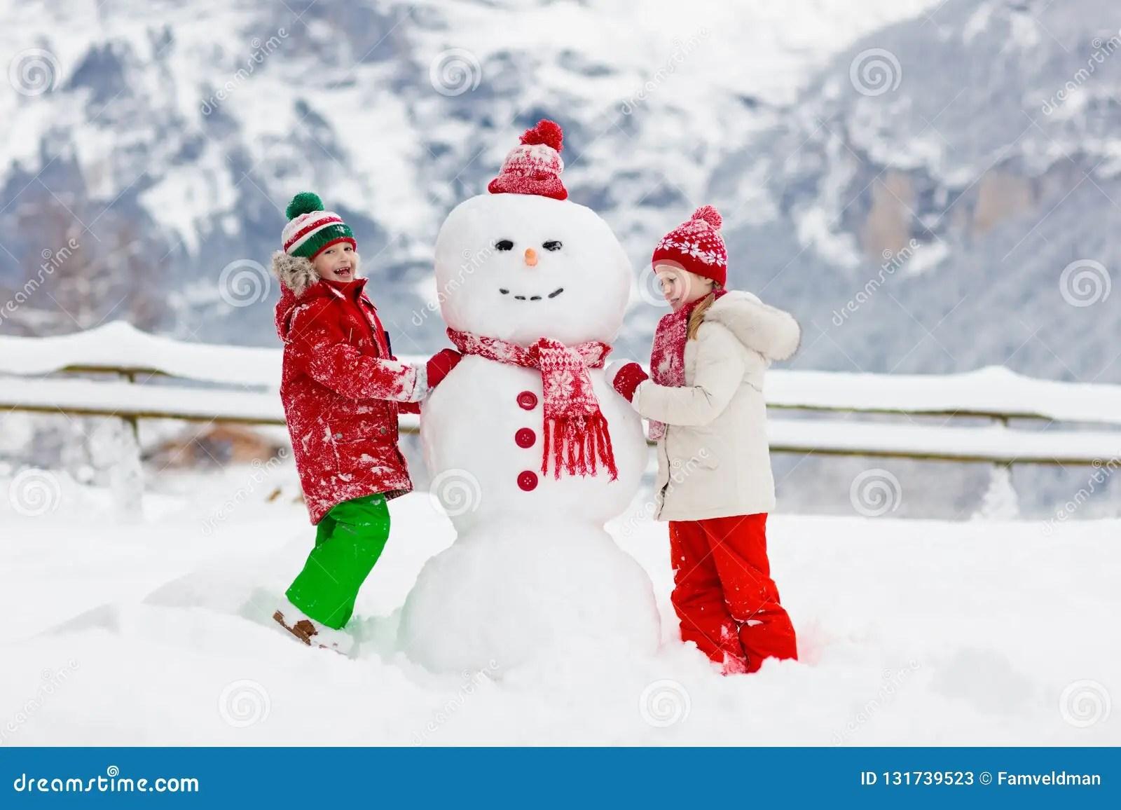 Child Building Snowman Kids Build Snow Man Boy And Girl