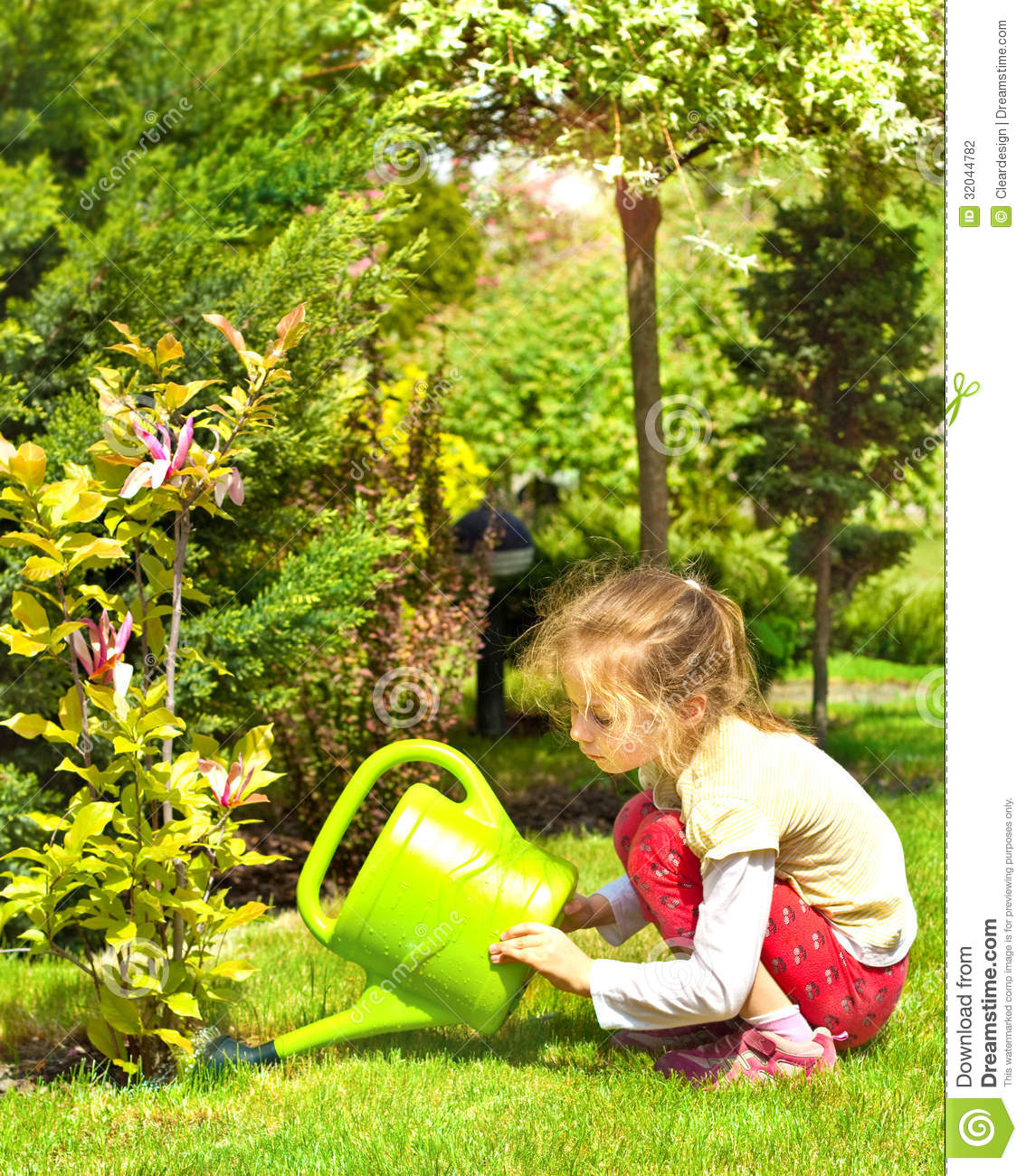 Child Girl Water Magnolia Flowers In The Garden Stock Photography