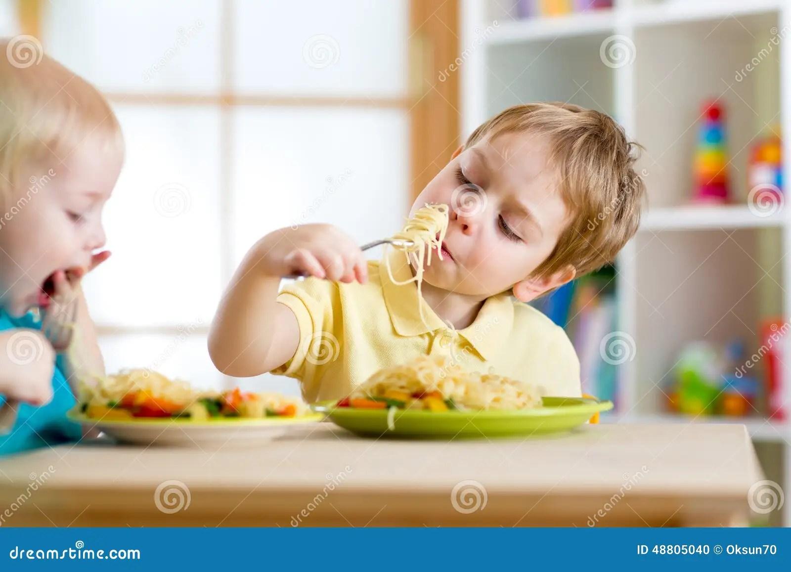 Children Eating Healthy Food In Kindergarten Or Stock