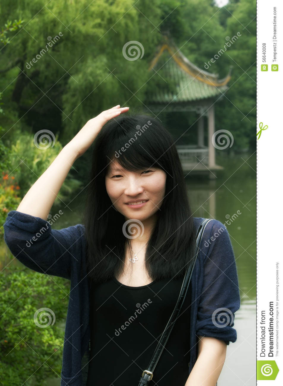 Chinese Woman Smiling And Patting Her Head Stock Photo