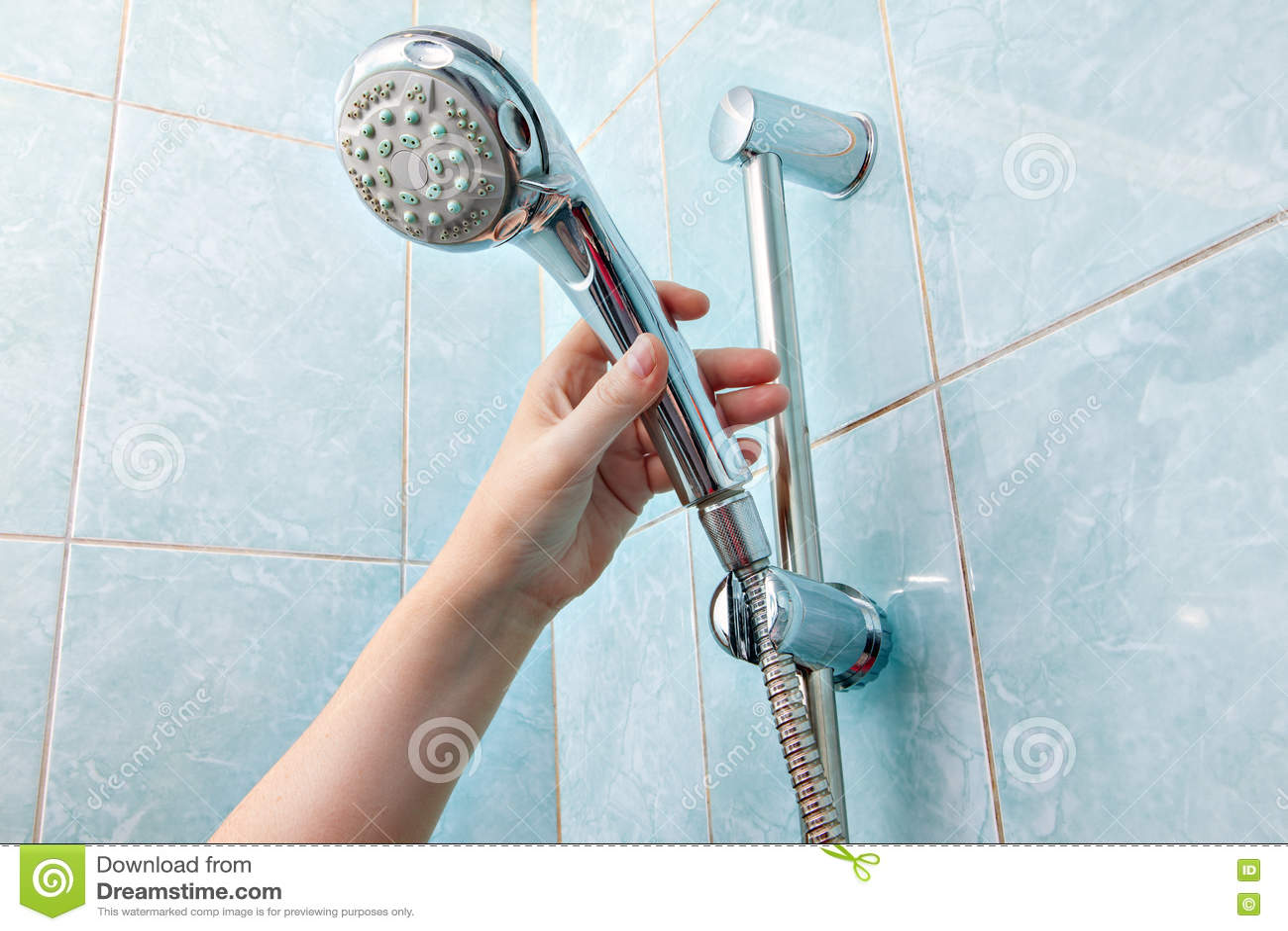 Close Up Of Human Hand Adjusts Holder Shower Head With Hose