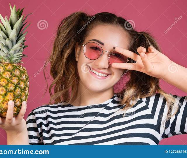 Close Up Portrait Of Beautiful And Kind Girl In Sunglasses Holds A Pineapple In Her Hand