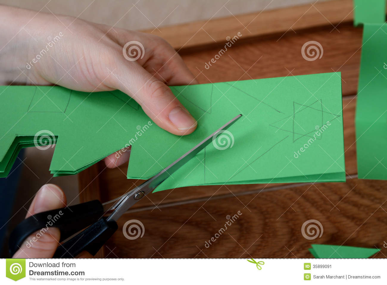Closeup Of Cutting A Christmas Tree Paper Chain Stock