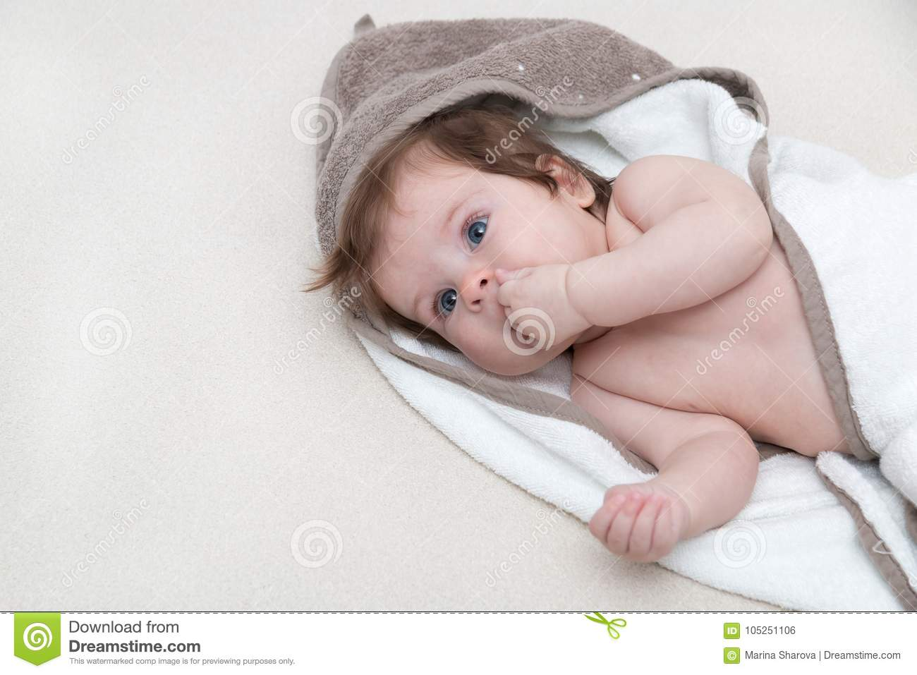 cute baby girl lying on a white bed blanket and keeps fingers in his