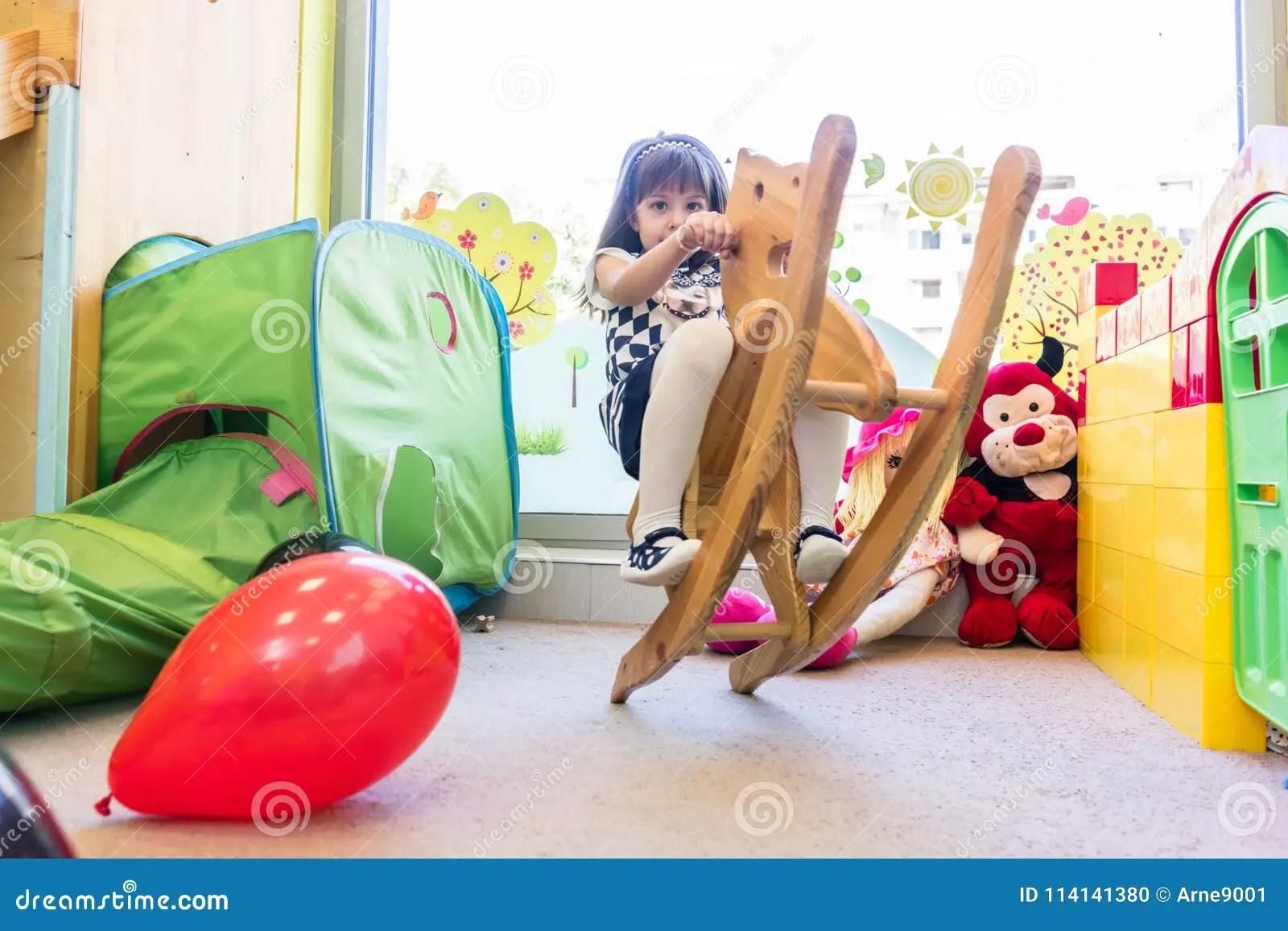 Cute Pre School Girl Swinging On A Vintage Wooden Horse