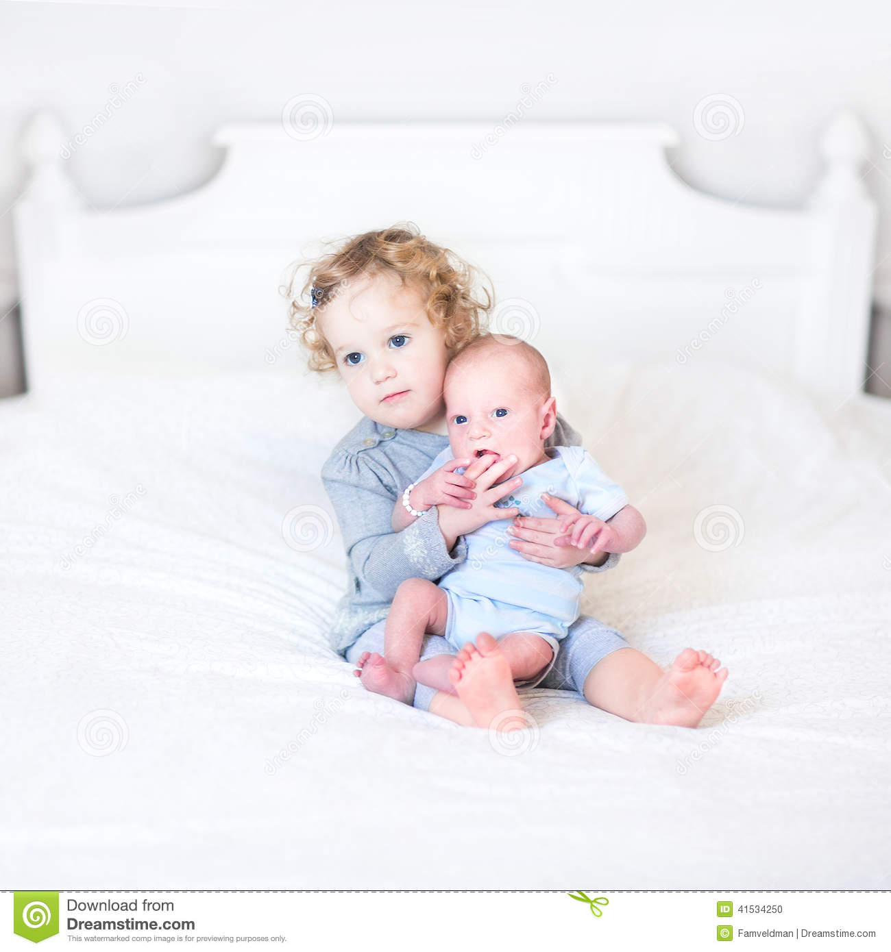 Cute Toddler Girl With Her Newborn Baby Brother Stock