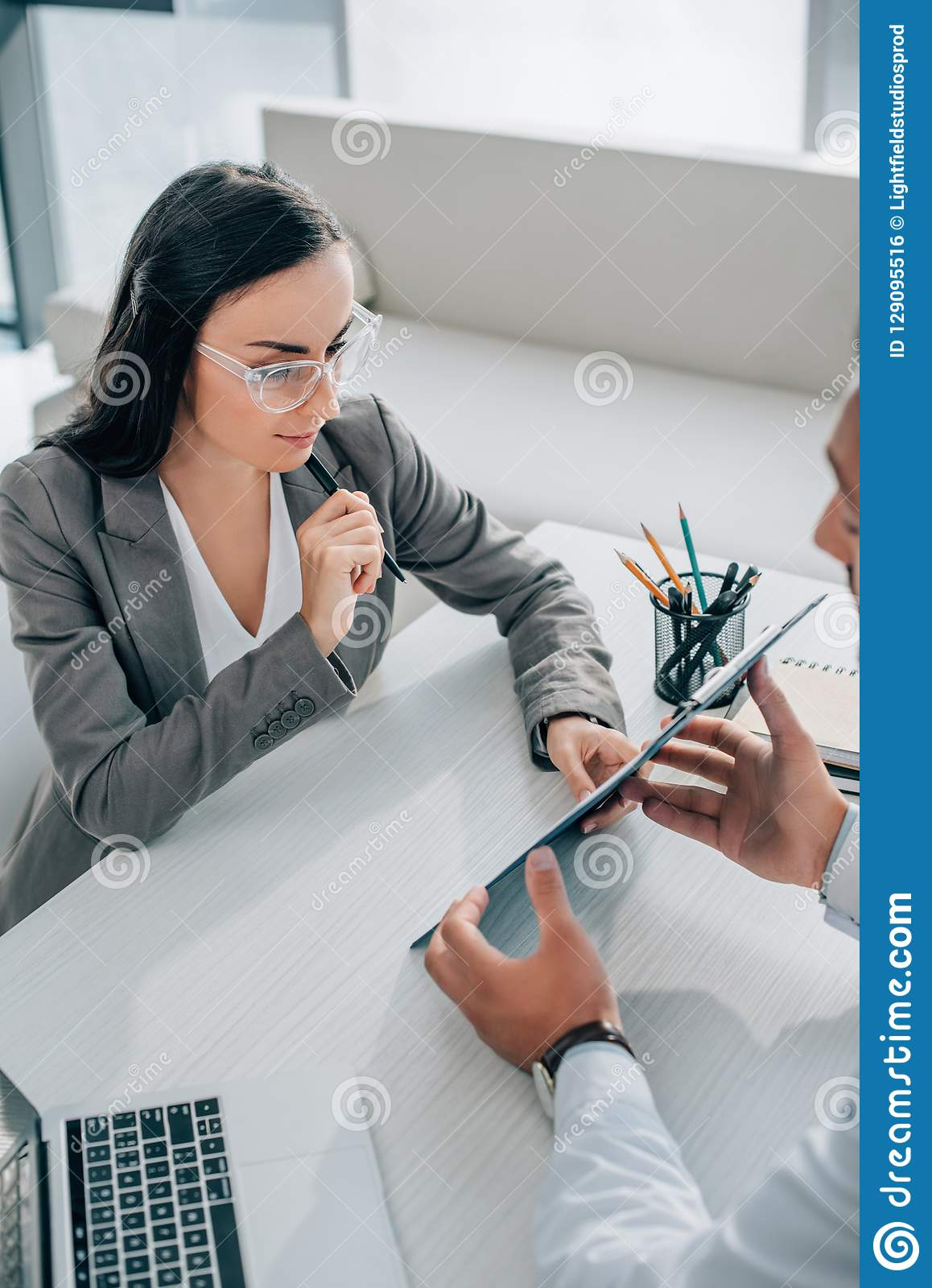 Doctor Showing Insurance Claim Form To Attractive Patient